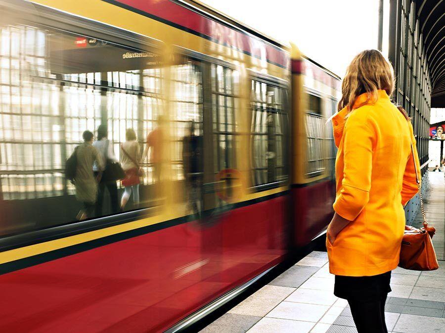 Eine Frau wartet auf die Bahn. Sie hat einen langen Arbeitsweg.
