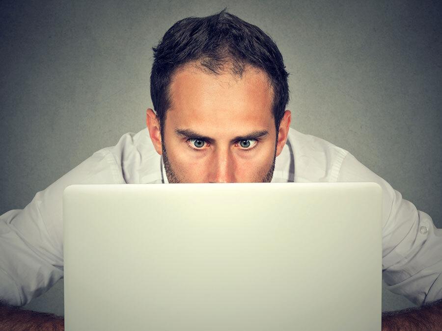 Ein Mann schaut schockiert auf den Bildschirm seines Laptops. Er hat soeben eine erhöhte Drittanbieterrechnung erhalten.
