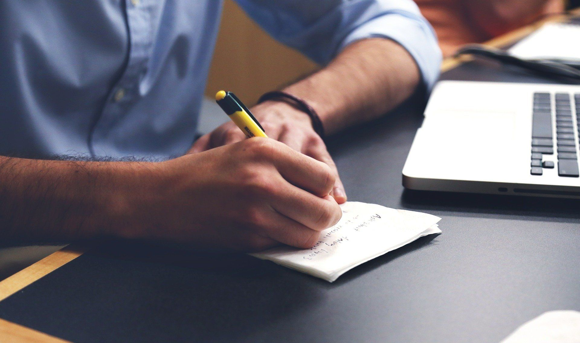 Ein Mann macht sich Notizen. Er möchte einen befristeten Arbeitsvertrag verlängern.