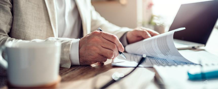 Ein Mieter unterschreibt einen Mietvertrag. Er schließt den Mietvertrag schriftlich ab.