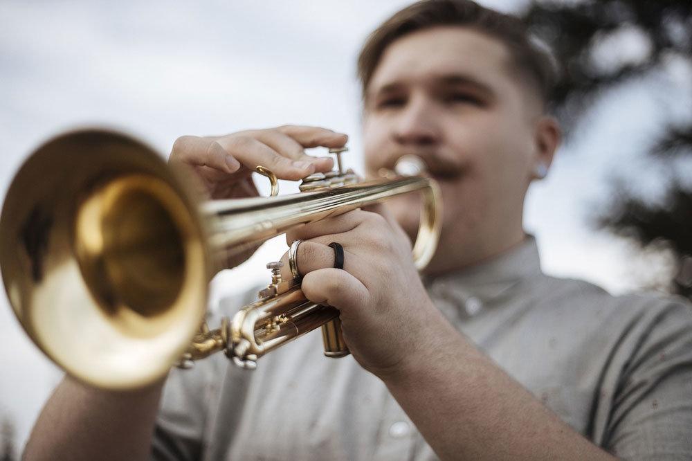 Ein Mann spielt Trompete und provoziert damit eine Beschwerde wegen Lärmbelästigung durch Nachbarn.