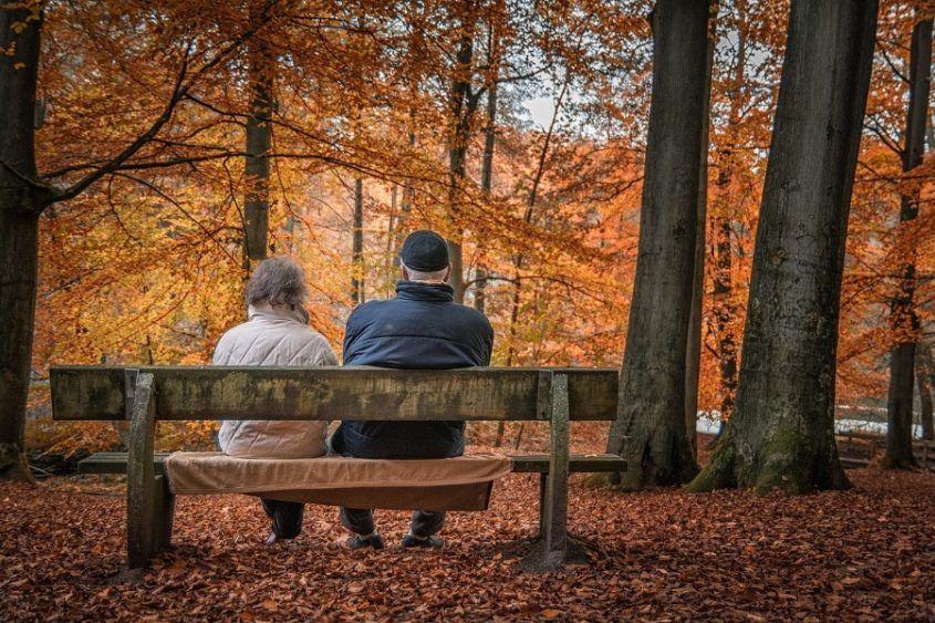 Ein älteres Ehepaar sitzt auf einer Bank und unterhält sich über das Berliner Testament.
