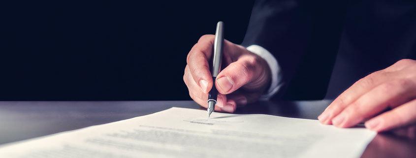 Ein Mann unterzeichnet sein Testament. Doch wie lange ist ein Testament gültig?