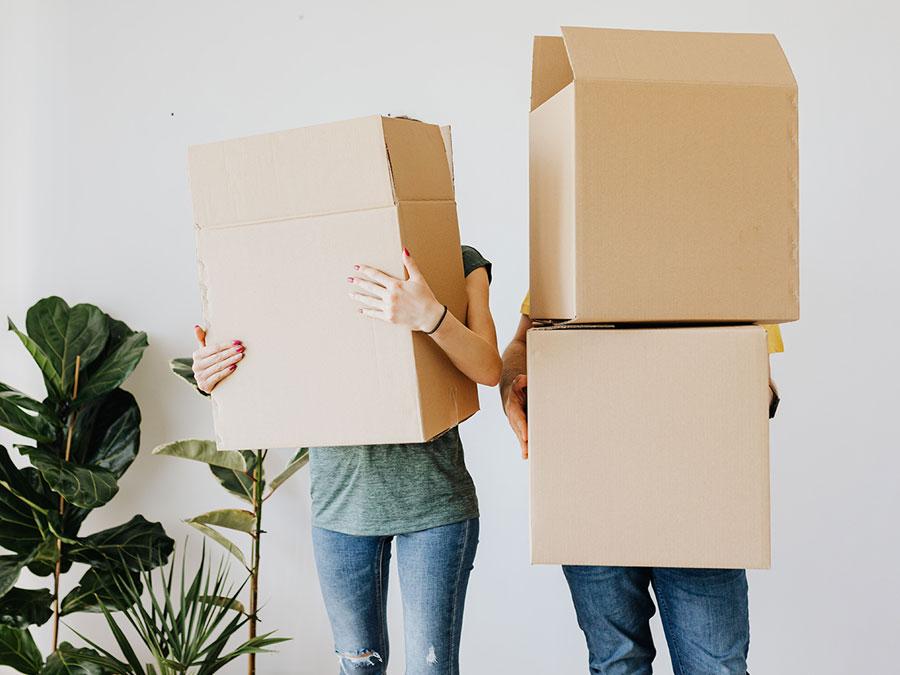 Ein Paar trägt Umzugskisten in die neue Wohnung. Zuvor haben Sie sich beim Vermieter über die Vormiete informiert.