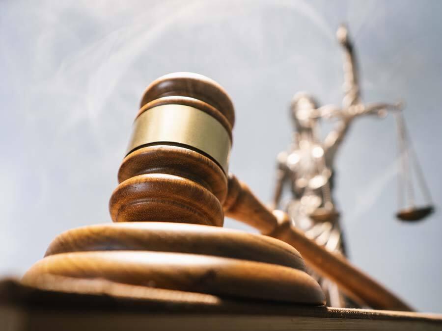 Richterhammer und Justizia symbolisieren ein Urteil.