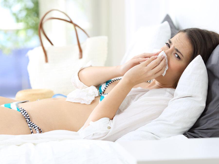 Eine Arbeitnehmerin ist trotz Krankheit in den Urlaub gefahren. Sie liegt im Bikini im Bett und schaubt sich die Nase.