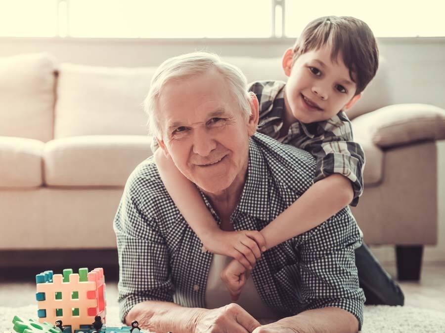 Ein Großvater spielt mit seinem Enkel und denkt über ein Vorausvermächtnis nach.