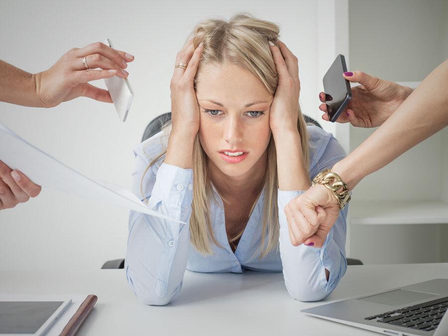 Eine Frau an ihrem Arbeitsplatz. Sie hält sich den Kopf, weil sie überlastet ist. Sie hat einen Burnout am Arbeitsplatz.