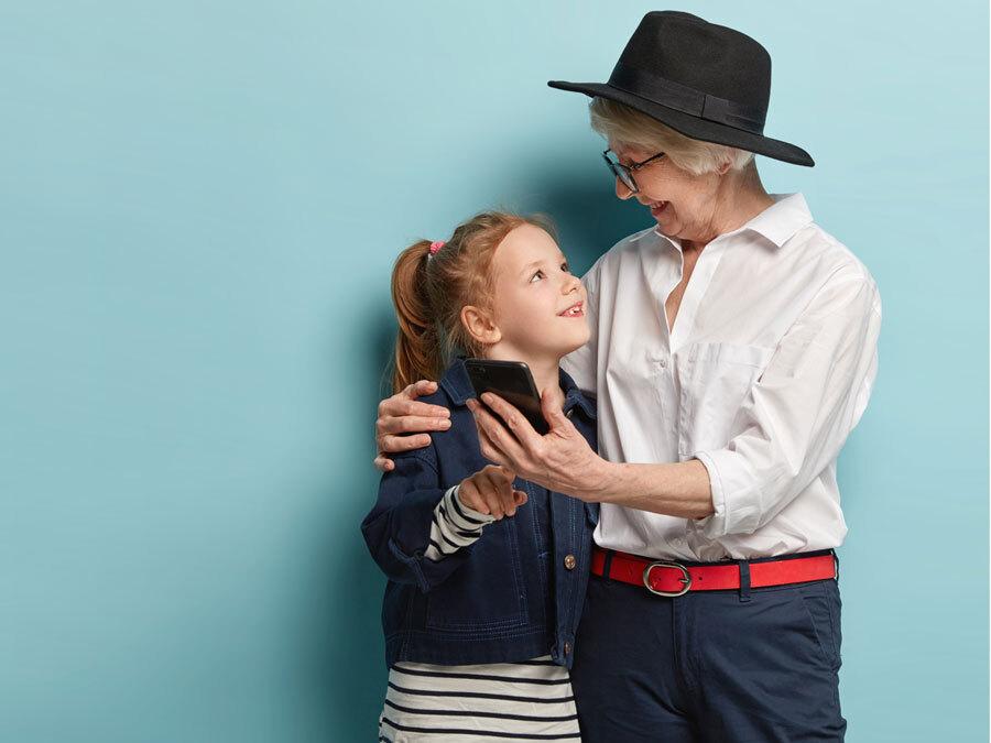 Eine ältere Dame hält ihre Enkelin im Arm. In der Hand hat sie ein Smartphone.