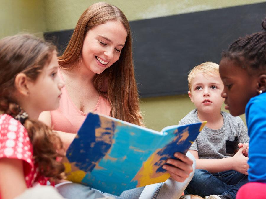 Eine Frau liest Kindern etwas vor. Sie arbeitet im Ehrenamt und kümmert sich um benachteiligte Kinder.
