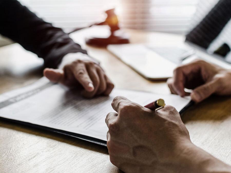 Ein Arbeitgeber zeigt auf die Unterschrift auf einer Kündigung in der Kurzarbeit.