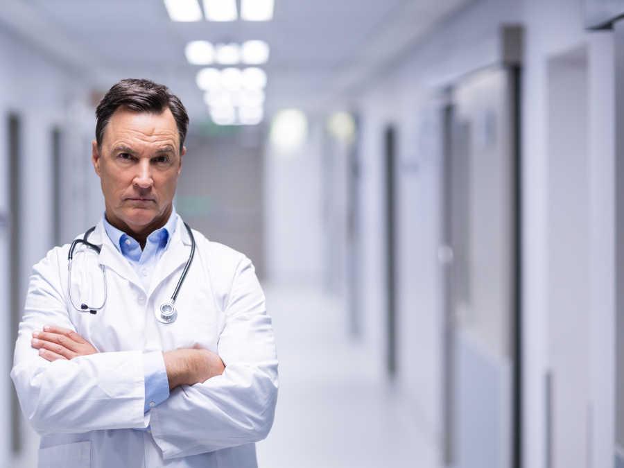 Ein Arzt mit besorgtem Blick steht im Flur eines Krankenhauses.
