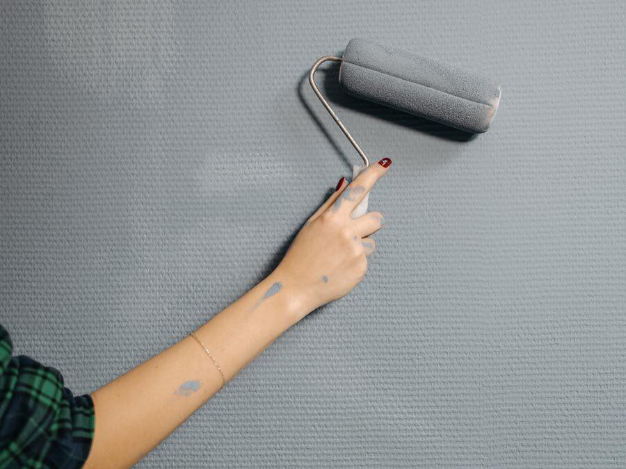 Eine Hand hält eine Malerrolle mit grauer Farbe. Es werden Schönheitsreparaturen ausgeführt.