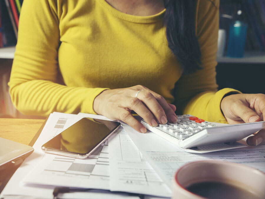 Eine junge Frau tippt auf einem Taschenrechner. Eine Studentin macht ihre Steuererklärung.