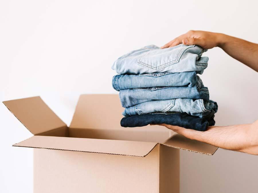 Ein Mieter packt seine Kleidung in eine Umzugskiste. Er hat seinen Zeitmietvertrag gekündigt.