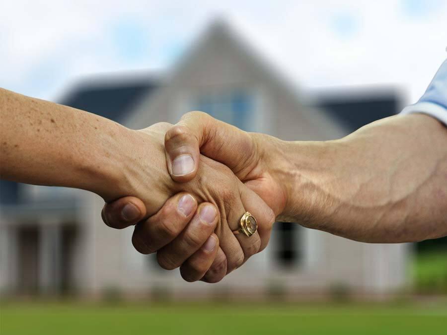 Vermieterin und Mieter geben sich die Hand. Sie wollen den Zeitmietvertrag verlängern.