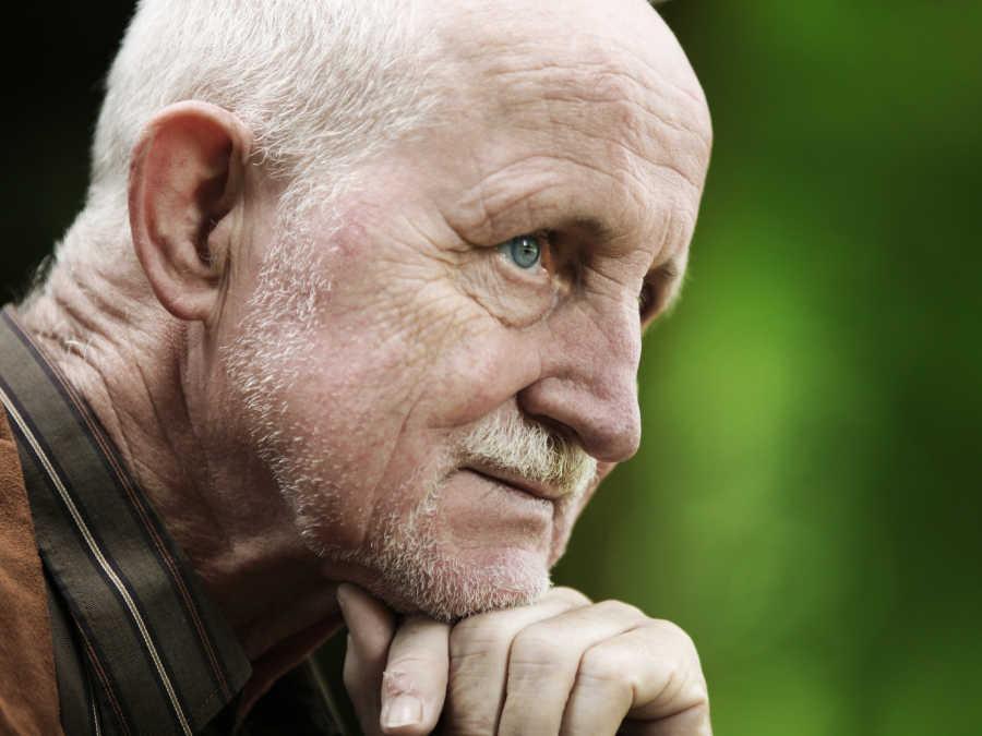 Ein älterer Herr schaut nachdenklich in die Ferne. Er beschäftigt sich gerade mit seiner Bestattungsverfügung.