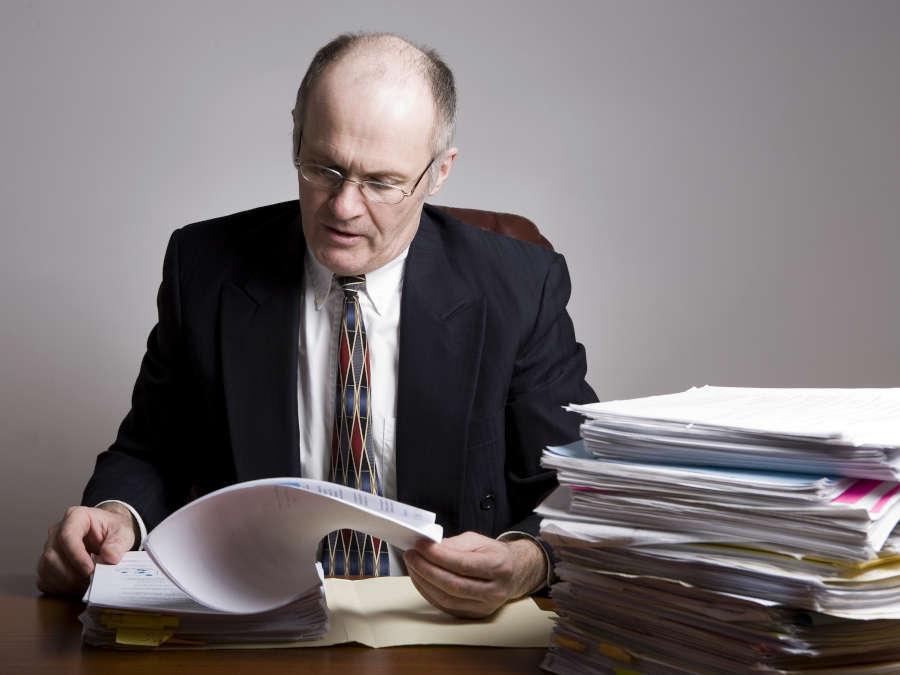 Ein Unternehmer blättert ins seinen Geschäftsunterlagen.