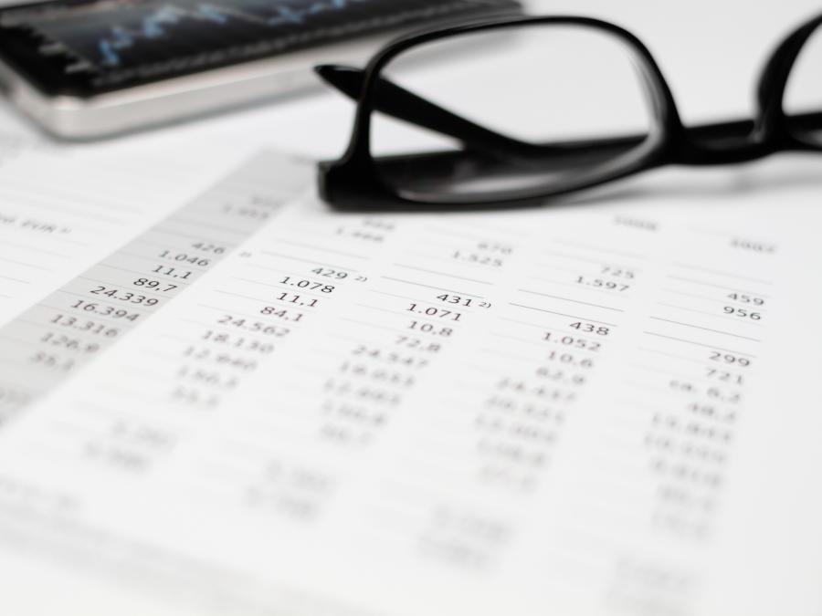 Eine lange Tabelle mit Zahlen und eine Brille liegen auf dem Tisch. Ein Arbeitnehmer der Kurzarbeitergeld bezogen hat muss Steuern nachzahlen.