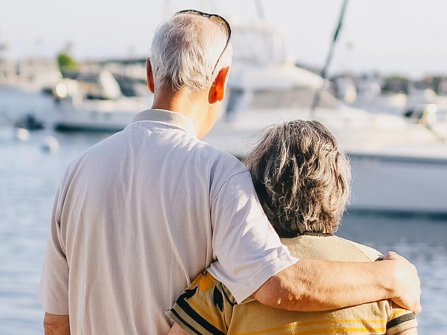 Ein älteres Paar steht am Hafen.