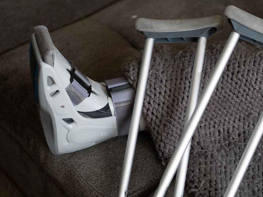 Ein Fuß mit Bandagen und zwei Krücken auf einem Sofa. Hier hatte jemand einen Arbeitsunfall im Homeoffice.