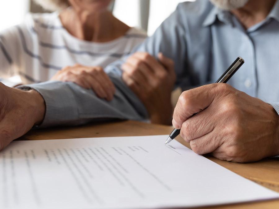 Ein Ehemann unterschreibt die Vollmacht für seine Frau.