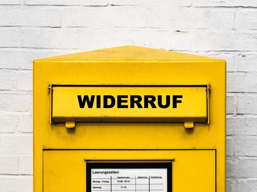 Ein gelber Briefkasten mit der Aufschrift Widerruf.