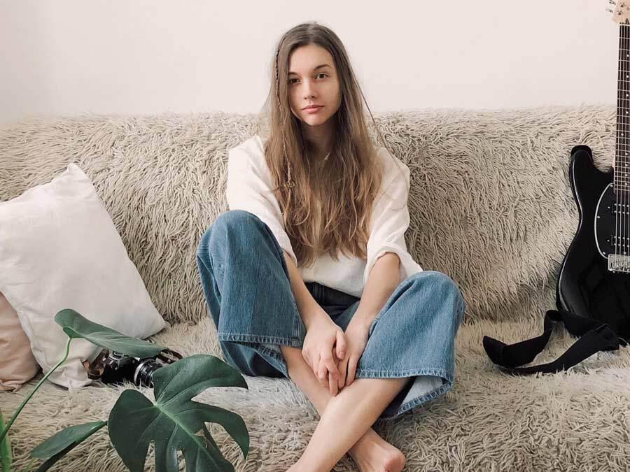 Eine junge Frau sitzt auf einem Sofa.