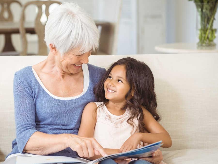 Eine Großmutter liest ihrer Enkelin ein Buch vor. Sie hat Großelternzeit beantragt.