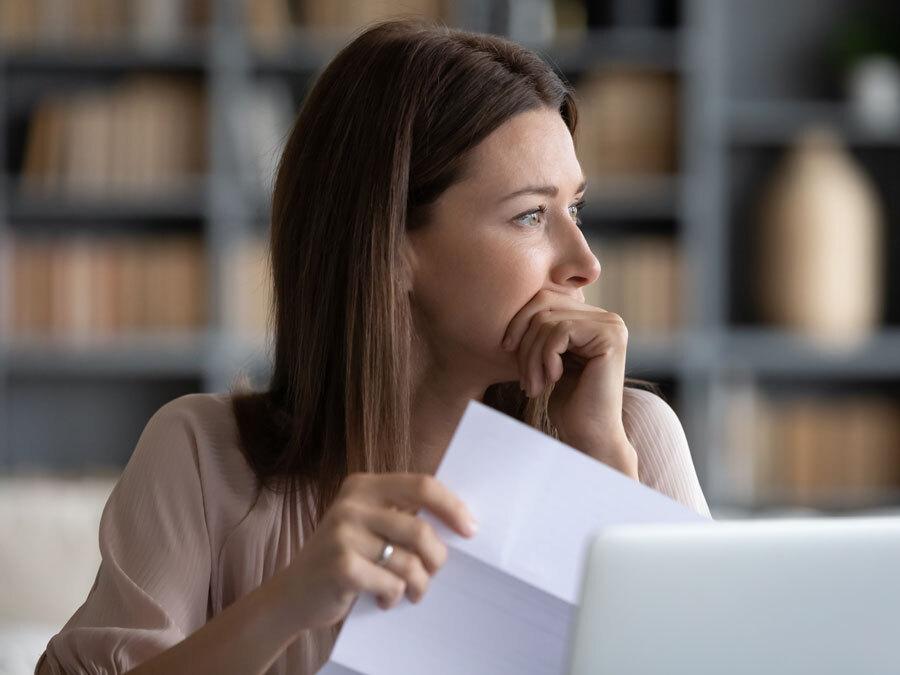 Eine Frau schaut nachdenklich aus dem Fenster. In der Hand hält sie das Schreiben eines Gläubigers. Wegen Erbschulden muss sie ein Nachlassinsolvenzverfahren einleiten.