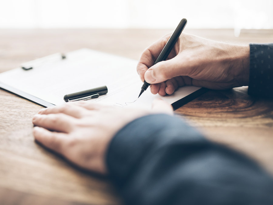 Mit dem Füller unterschreibt ein Mann sein Testament. Er sollte auch daran denken, das Datum im Testament neben die Unterschrift zu setzen.