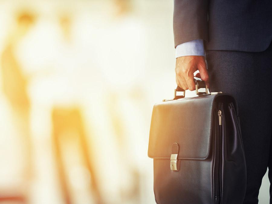 Ein Arbeitnehmer hält eine Aktentasche in der Hand. Er will eine Versetzung auf eigenen Wunsch durchsetzen.