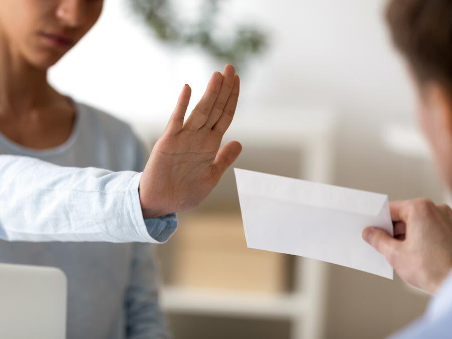 Annahmeverweigerung der Kündigung. Eine Frau weist mit der Hand einen Brief zurück.