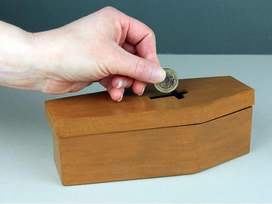 Symbolisch legt eine Hand Geld in eine Spardose. Die Spardose ist wie ein Sarg geformt. Beerdigungskosten sind teuer.