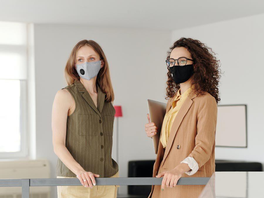 Zwei Frauen stehen mit einer Maske zum Schutz vor Corona im Büro.