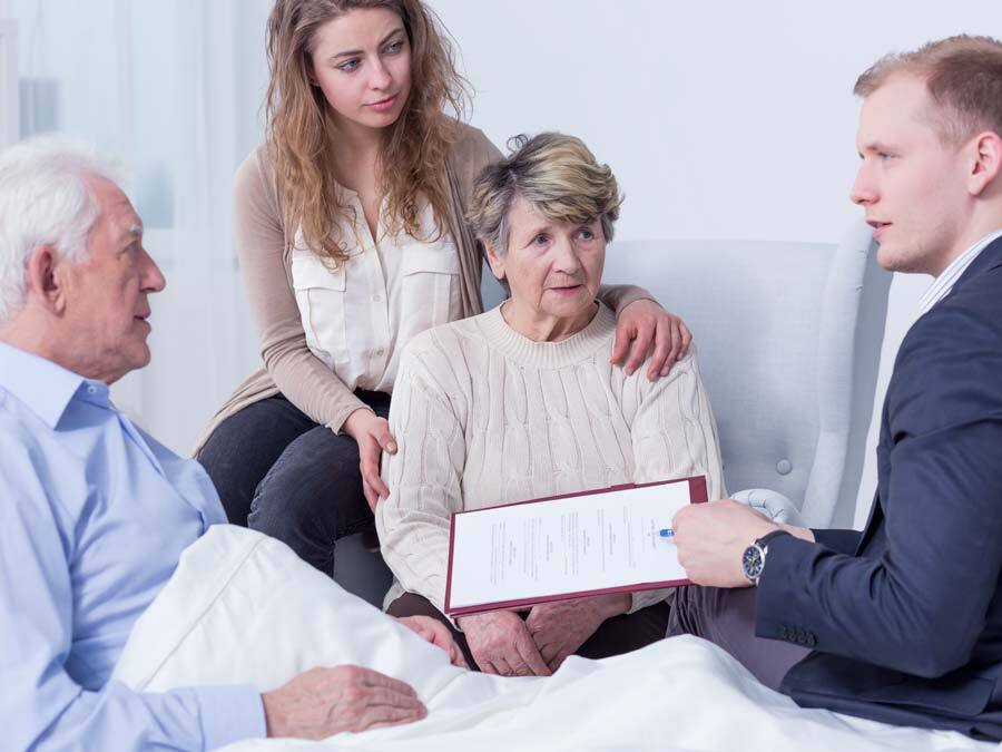Ein schwerkranker Mann liegt im Krankenbett. Um ihn herum drei Personen. Sie errichten ein Nottestament.