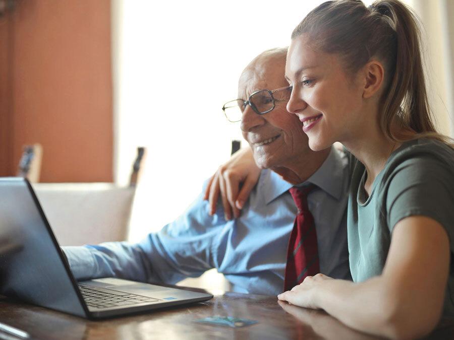 Ein älterer Herr sitzt mit seiner Tochter am Rechner. Sie prüfen den Pflegevertrag.