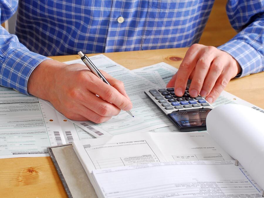 Ein Mann mit einem Taschenrechner ist dabei seine Steuererklärung auszufüllen.