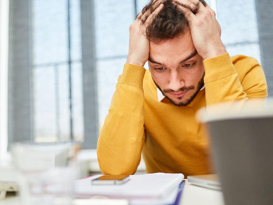 Ein Angestellter mit verzweifeltem Blick starrt auf seinen Schreibtisch. Er plant eine Eigenkündigung wegen Krankheit.