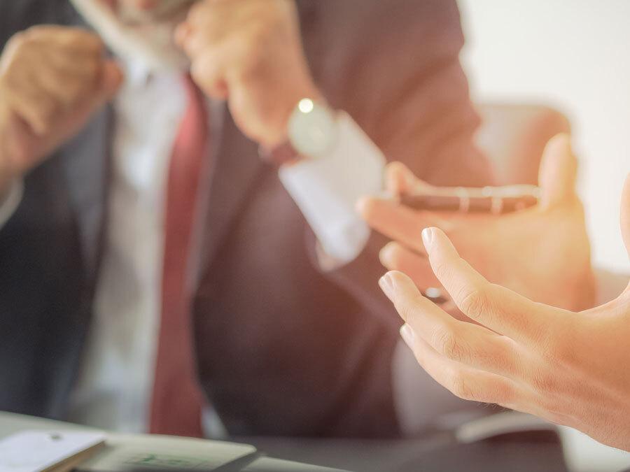 Man sieht einen Bildausschnitt mit Händen von zwei Menschen, die heftig diskutieren. Es geht darum, ob man ein Testament anfechten kann.
