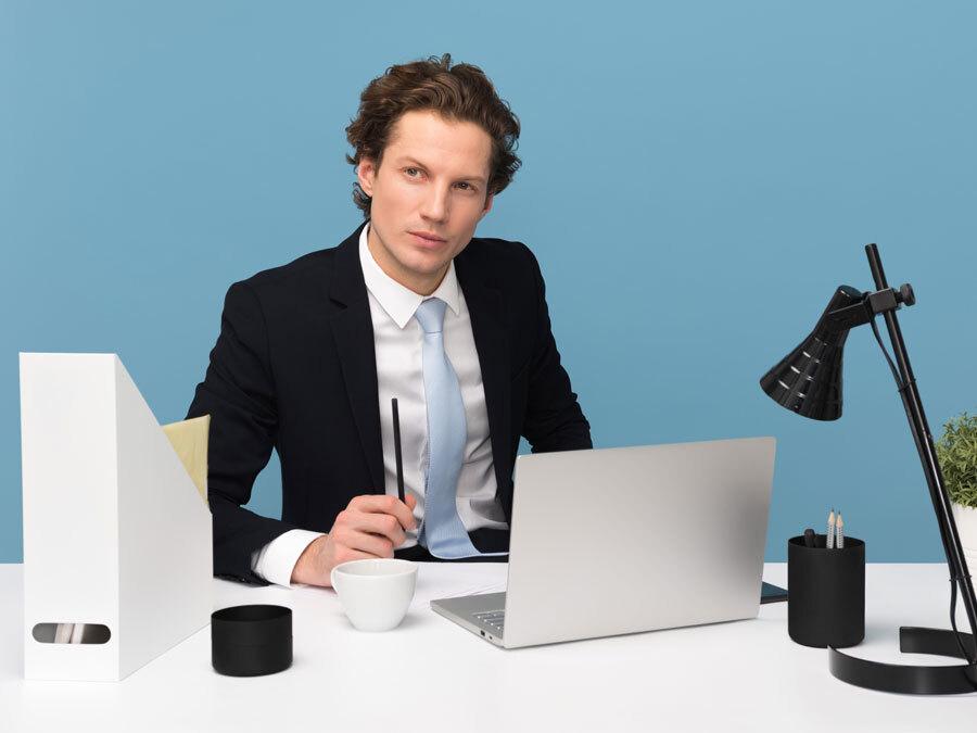 Ein Mann mit unsicherem Gesichtsausdruck sitzt Rechner. Er kann nicht Nein sagen.