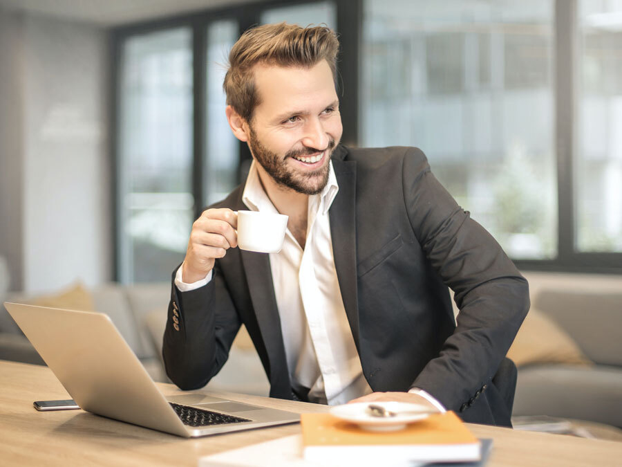 Ein Mann sitzt vor einem Rechner und macht gerade ein Kaffeepause. Er nutzt eine Methode zum Stessabbau.