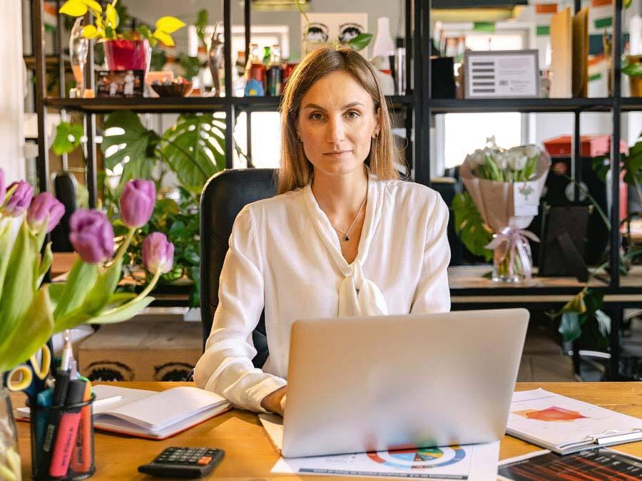 Eine Frau im Homeoffice sitzt vor dem Rechner. Sie plant den Tagesablauf.