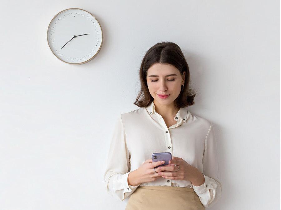 Eine Frau steht unter einer Uhr und tippt auf ihr Smartphone. Sie hat Probleme mit dem Zeitmanagagement.