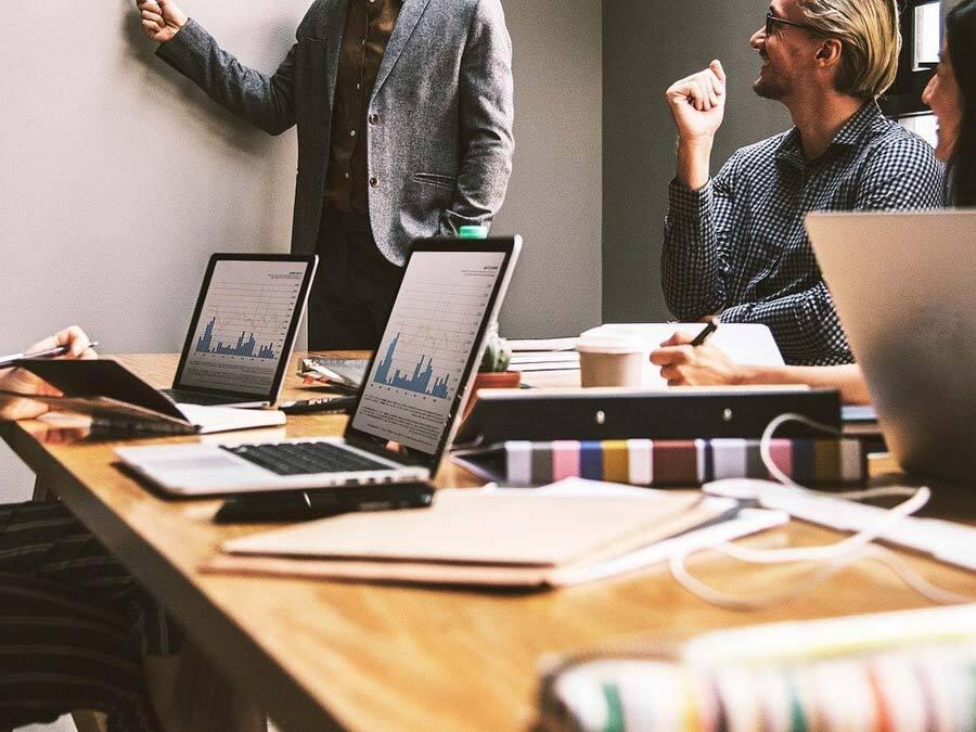 Zwei Laptops auf einem Schreibtisch und Arbeitsutensilien. Ein Team setzt sich SMART formulierte Ziele.