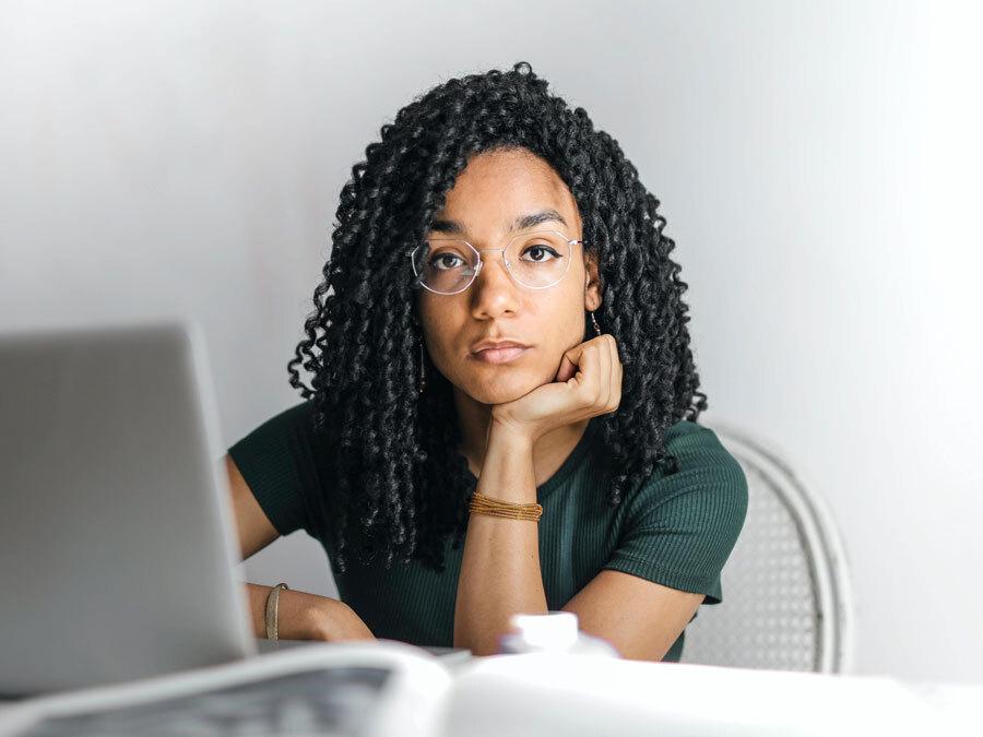 Eine Frau sitzt an ihrem Schreibtisch und kämpft mit anhaltender Unzufriedenheit im Job.