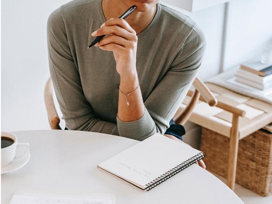Eine Frau sitzt nachdenklich vor einem leeren Blatt Papier.