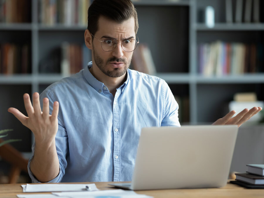 Ein Mann sitzt vor einem Laptop macht ein verzweifeltes Gesicht. Es gab eine Datenpanne.