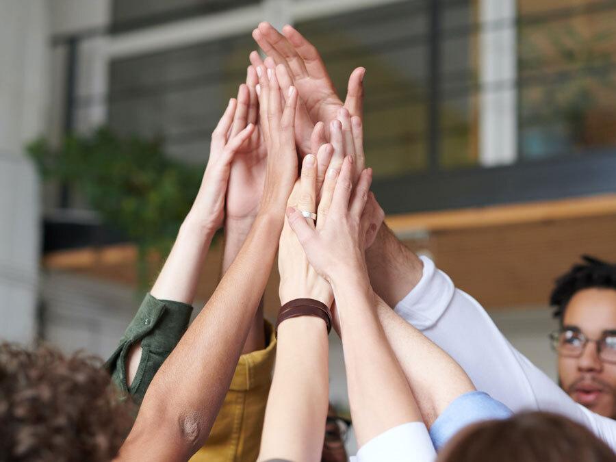 Mehrere Personen klatschen sich in die Hände. Sie freuen sich über die Werte im Unternehmen