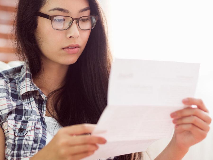 Eine Frau mit Brille hält ein Schreiben in der Hand. Es ist eine Datenschutz Einwilligung.